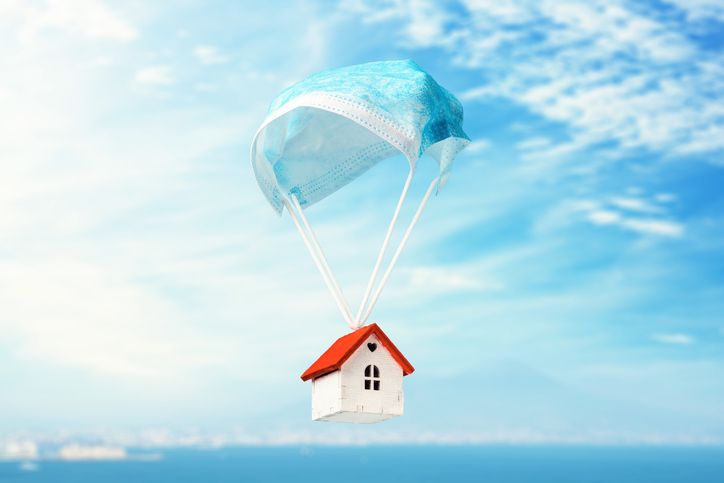 A toy house flies on a parachute from a medical mask. The concept of a protected house from viruses (Photo credit: Getty Images/ SergeyChayko)