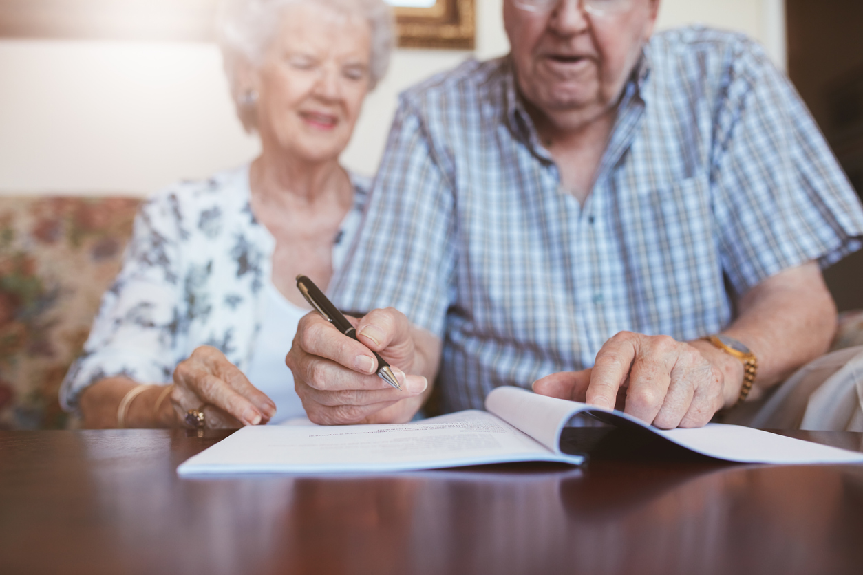 Older couple signing document. Credit: iStock.com/jacoblund
