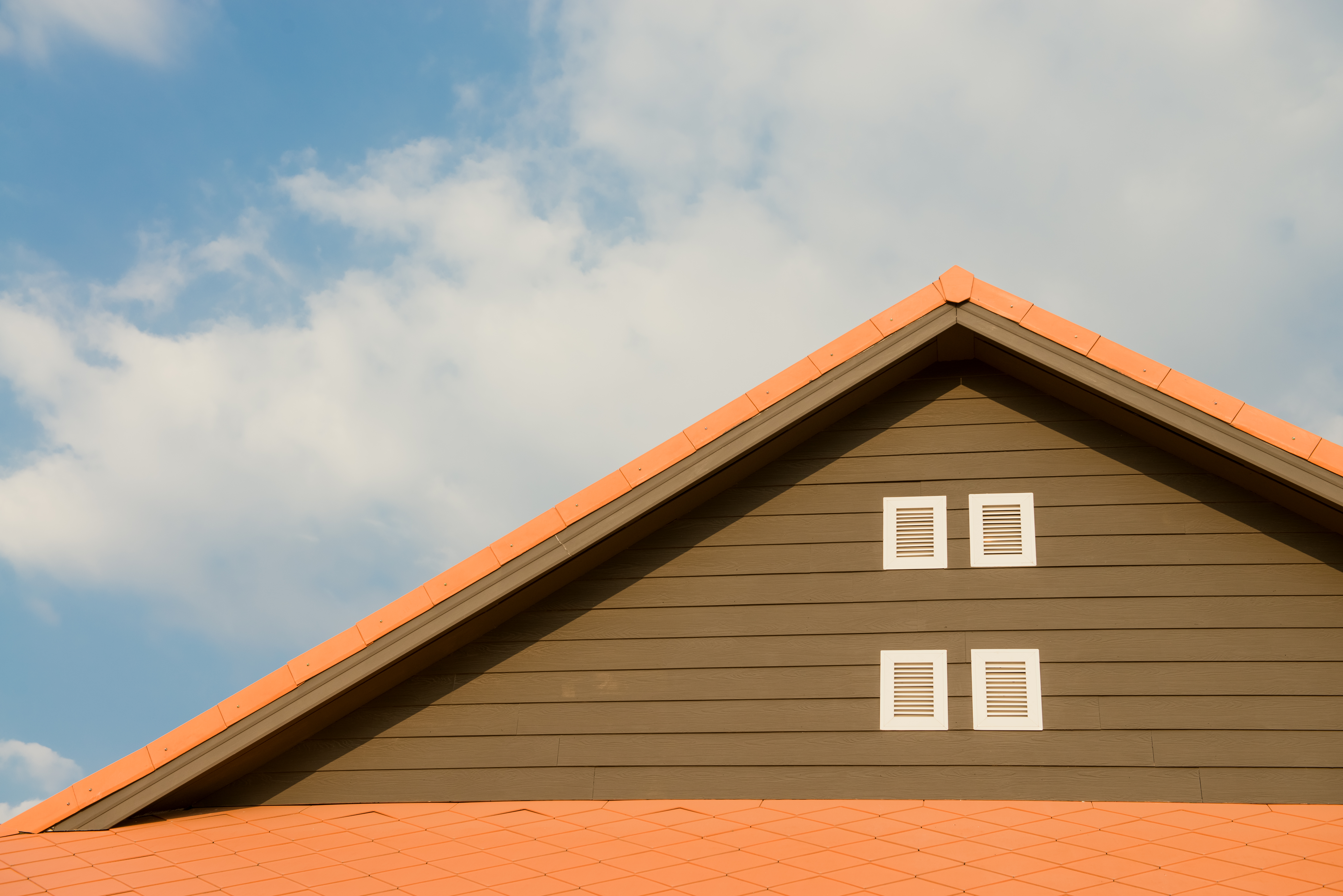 Orange and gray roof under blue sky with white clouds.