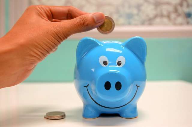 Person putting coin in blue Piggy Bank.