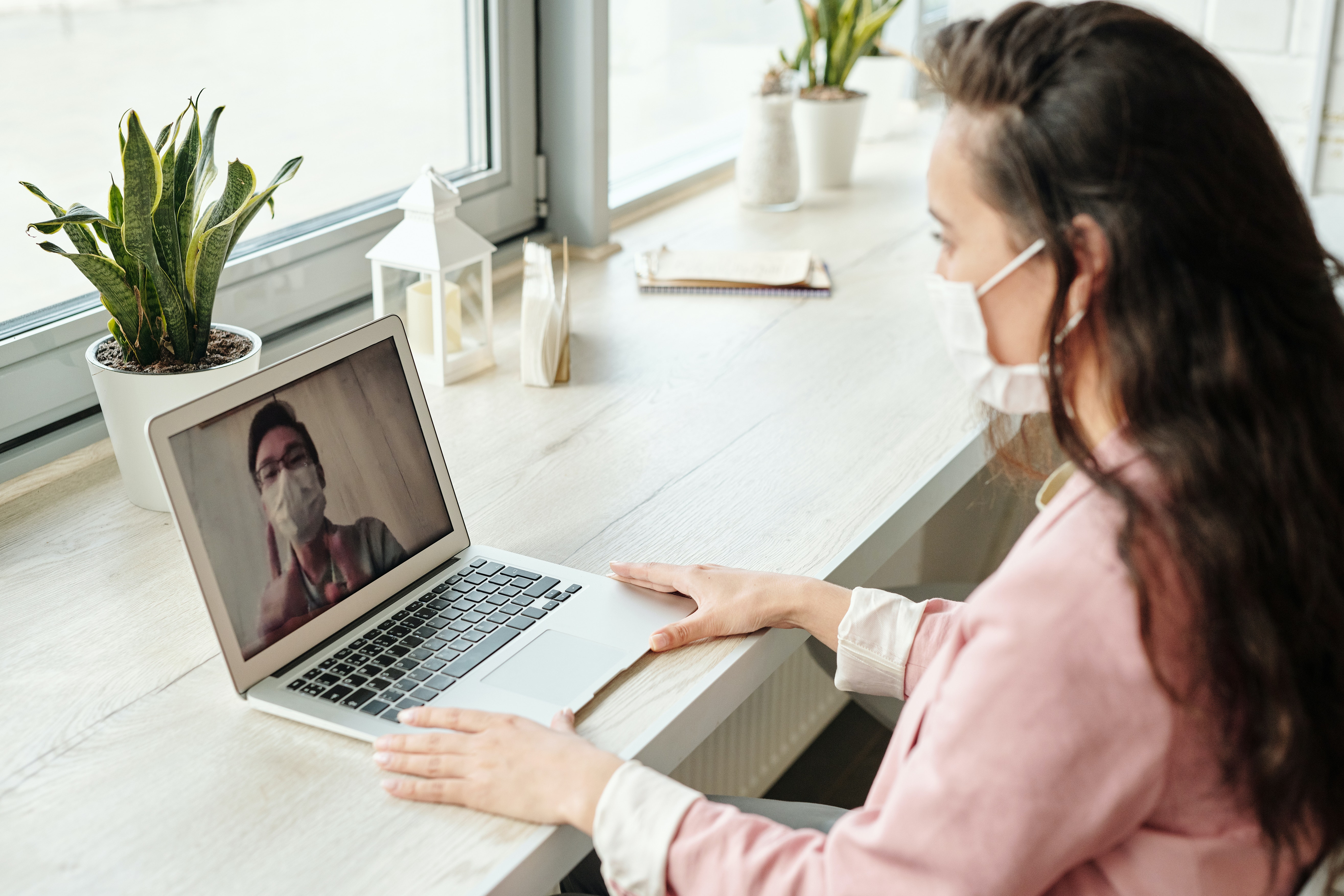 Woman working from home with face mask on.